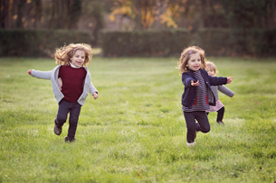 Three smiling young girls running across a lawn.の写真素材 [FYI02859036]