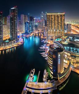 Cityscape of Dubai, United Arab Emirates at dusk, with illuminated skyscrapers lining the Dubai Creeの写真素材 [FYI02859045]
