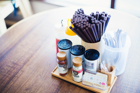 A ramen noodle shop counter with chopsticks and condiments.の写真素材 [FYI02859053]