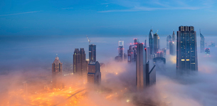Cityscape with illuminated skyscrapers above the clouds in Dubai, United Arab Emirates at dusk.の写真素材 [FYI02859054]