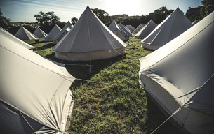 Glamping bell tents, traditional canvas tents in an enclosure on the camping grounds at an outdoor mの写真素材 [FYI02859061]