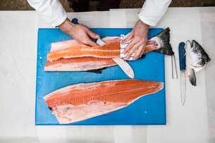High angle close up of fishmonger standing at a table, cutting and filleting fresh salmon on blue chの写真素材 [FYI02859069]
