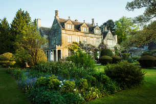 Exterior view of a 17th century Cotswold stone country house from a garden with flower beds, shrubsの写真素材 [FYI02859070]