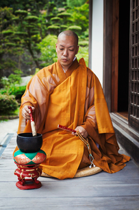 Buddhist monk with shaved head wearing golden robe sitting on floor outdoors, using singing bowl.の写真素材 [FYI02859094]