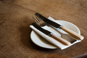 Close up high angle view of plate with knives and fork and a serviette on a rustic wooden table.の写真素材 [FYI02859096]