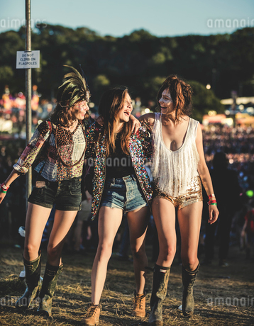 Three young women at a summer music festival wearing hot pants and Wellington boots, feather headdreの写真素材 [FYI02859115]