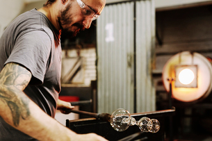 A glassblower holding a blown glass on the end of a pipe, and shaping it.の写真素材 [FYI02859141]