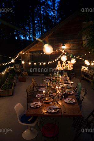 String lights illuminating food on dining table at nightの写真素材 [FYI02859161]