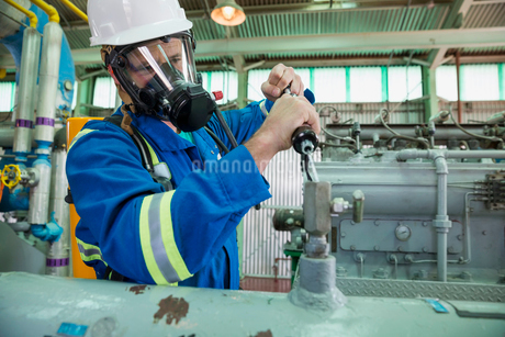 Male worker repairing equipment in gas plantの写真素材 [FYI02859224]