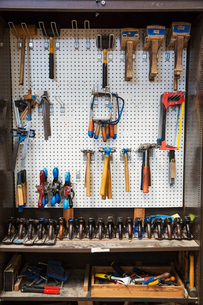 Work bench in a boat-builder's workshop, selection of hand tools for wood working hanging on a wall.の写真素材 [FYI02859249]