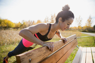Jogger doing push-ups on park benchの写真素材 [FYI02859254]
