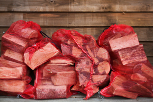 Close up of a stack of firewood in red net bags outside a farm shop.の写真素材 [FYI02859256]