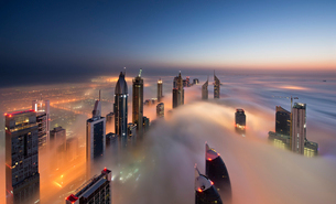 View of illuminated skyscrapers above the clouds in Dubai, United Arab Emirates at dusk.の写真素材 [FYI02859260]