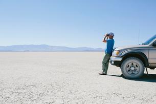 Man standing on vast desert, looking through binoculars and leaning against truck, Black Rock Desertの写真素材 [FYI02859275]