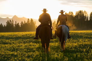 Two cowboys riding on horseback in a Prairie landscape at sunset.の写真素材 [FYI02859276]