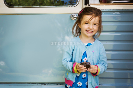 Smiling girl standing in front of blue mobile coffee shop, holding chocolate brownie.の写真素材 [FYI02859278]
