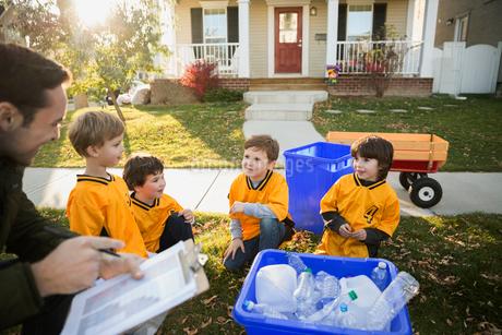 Coach and boys sports team gathering recycling neighborhoodの写真素材 [FYI02859286]