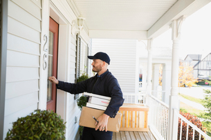 Delivery man with packages knocking at front doorの写真素材 [FYI02859293]