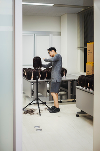 Bearded man wearing glasses standing indoors, cutting hair of brown wig on mannequin head.の写真素材 [FYI02859299]