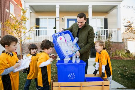 Coach and boys sports team gathering recycling neighborhoodの写真素材 [FYI02859301]