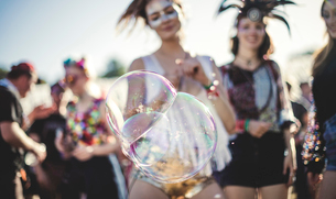 Revellers at a summer music festival large soap bubbles in foreground.の写真素材 [FYI02859317]