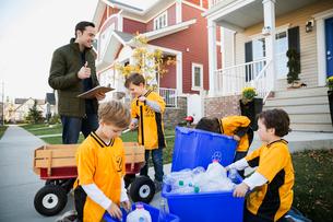 Coach and boys sports team gathering recycling neighborhoodの写真素材 [FYI02859336]