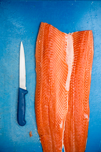 High angle close up of fillets of fresh salmon and knife on blue chopping board.の写真素材 [FYI02859365]