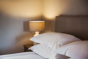 A cosy bedroom decorated in neutral colours, with a double bed and bedside lights on. Hospitality.の写真素材 [FYI02859384]