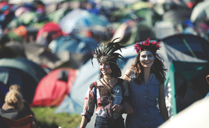 Two smiling young women at a summer music festival face painted, wearing feather headdress, standingの写真素材 [FYI02859403]