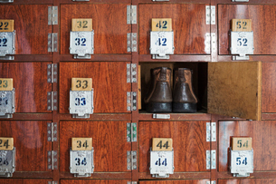 One pair of shoes in a shoe locker with an open door. Lockers in a row, with numbers.の写真素材 [FYI02859425]