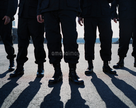 Low angle view of row of men wearing military uniforms, casting shadowsの写真素材 [FYI02859440]