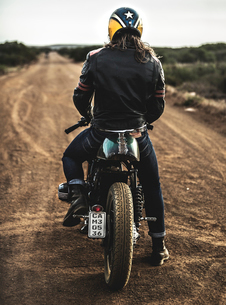 Rear view of man wearing crash helmet sitting on cafe racer motorcycle on a dusty dirt road.の写真素材 [FYI02859453]