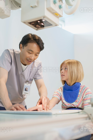 x-ray technician adjusting position of young patients handの写真素材 [FYI02859461]