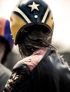 Rear view of man wearing yellow and blue crash helmet and black leather jacket.の写真素材 [FYI02859467]