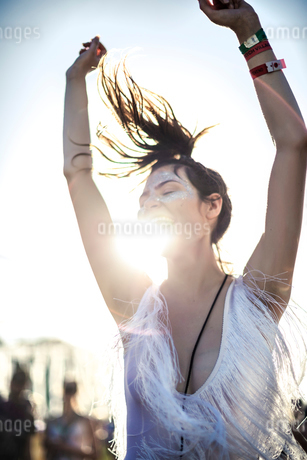 Young woman in a white fringed top dancing at a summer music festival with arms raised and long hairの写真素材 [FYI02859468]