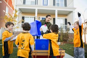 Coach and boys sports team gathering recycling neighborhoodの写真素材 [FYI02859473]