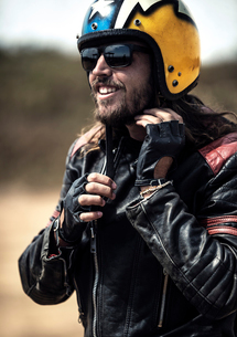 Bearded man wearing black leather jacket and sunglasses adjusting his yellow open face crash helmet.の写真素材 [FYI02859481]