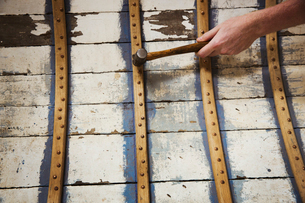 Close up of person in a boat-builder's workshop, working on a wooden boat hull.の写真素材 [FYI02859484]