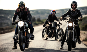 Three men wearing open face crash helmets and goggles sitting on cafe racer motorcycles on a rural rの写真素材 [FYI02859488]