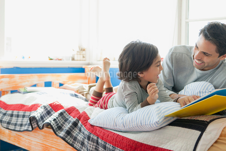 father and young son smiling while reading a bookの写真素材 [FYI02859492]