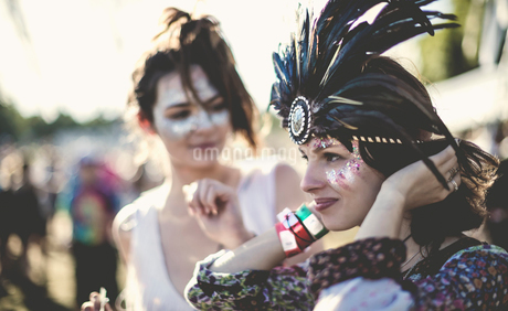 Two young women at a summer music festival faces painted, wearing feather headdress.の写真素材 [FYI02859590]