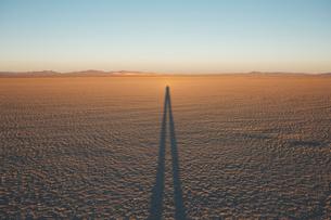 Man standing on Black Rock Desert Playa at dusk, casting long shadow, Nevadaの写真素材 [FYI02859601]