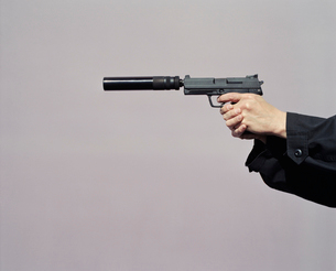 Detail of man aiming high powered hand gun with silencerの写真素材 [FYI02859606]