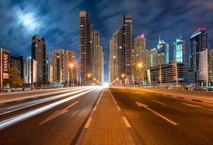 Cityscape with illuminated skyscrapers in Dubai, United Arab Emirates at dusk, highway in foregroundの写真素材 [FYI02859613]