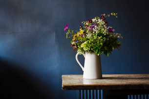 Close up of white jug with bunch of wild flowers on a wooden table, blue wall behind.の写真素材 [FYI02859614]