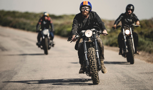 Three men wearing open face crash helmets and goggles riding cafe racer motorcycles along rural roadの写真素材 [FYI02859648]