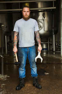 Man standing in a brewery, holding a mallet and a large metal wrench.の写真素材 [FYI02859654]