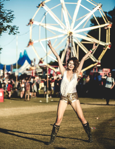 Young woman at a summer music festival wearing golden sequinned hot pants, face painted, smiling atの写真素材 [FYI02859669]