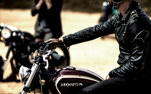 Side view of man wearing black leather jacket sitting on cafe racer motorcycle on a dusty dirt road.の写真素材 [FYI02859670]