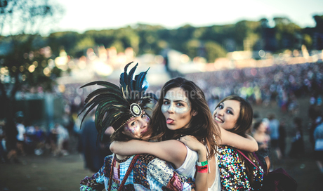 Three young women at a summer music festival feather headdress and faces painted, smiling at camera,の写真素材 [FYI02859671]